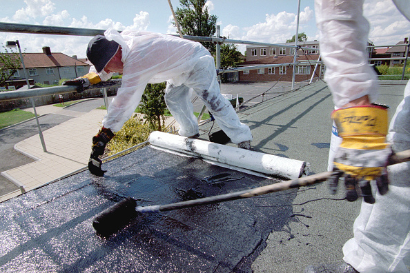 Bituminous Coal「Two workers laying bituminous roofing on a flat roof」:写真・画像(1)[壁紙.com]