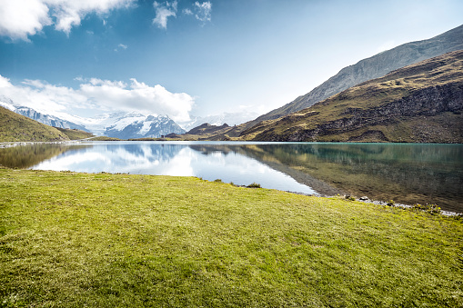 European Alps「Grassy patch next to lake with mountain reflections」:スマホ壁紙(6)