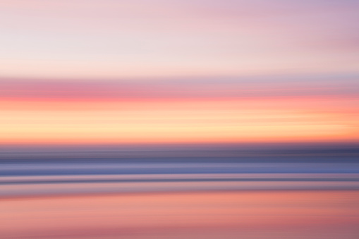 Motion「Defocused view of ocean waves on beach under sunset sky」:スマホ壁紙(9)