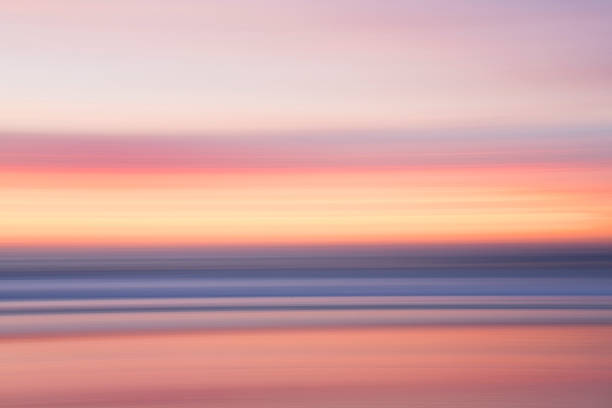 Defocused view of ocean waves on beach under sunset sky:スマホ壁紙(壁紙.com)