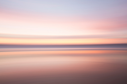 Leaving「Defocused view of ocean waves on beach under sunset sky」:スマホ壁紙(3)