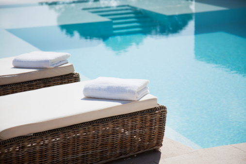 Spain「Folded towels on lounge chairs beside pool」:スマホ壁紙(3)