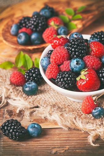 Raspberry「Fresh berries in a bowl on rustic wooden background.」:スマホ壁紙(12)