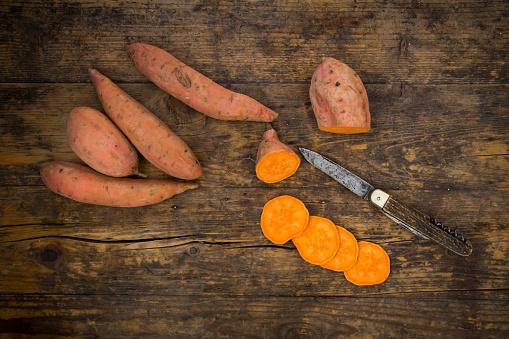 Sweet Potato「Sliced and whole sweet potatoes on dark wood」:スマホ壁紙(8)