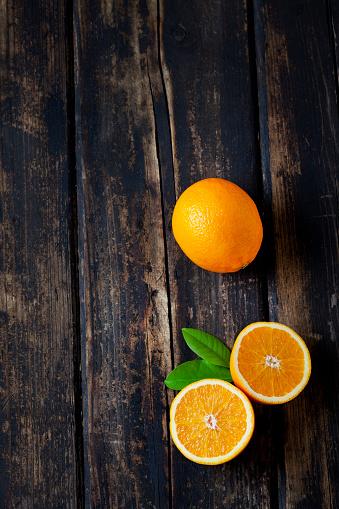 Orange - Fruit「Sliced and whole orange on dark wood」:スマホ壁紙(0)