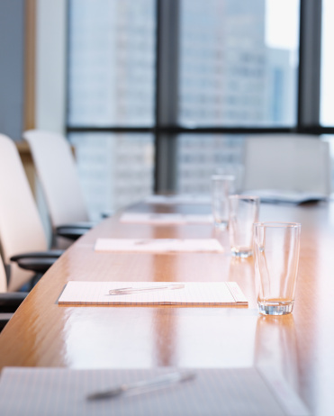 Meeting「Empty boardroom table with notepads and glasses on it」:スマホ壁紙(1)