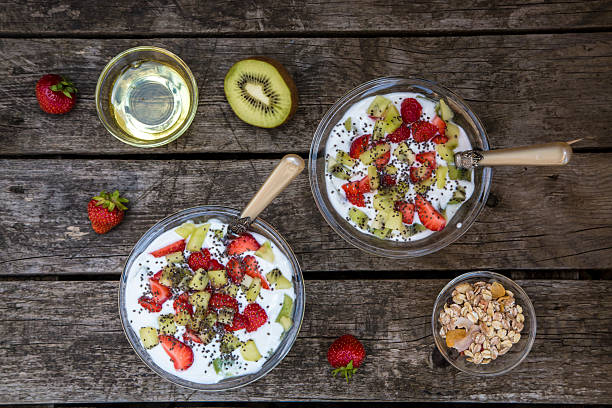 Strawberry kiwi yogurt with cereals, chia seeds, agave syrup in glass bowl on wood:スマホ壁紙(壁紙.com)