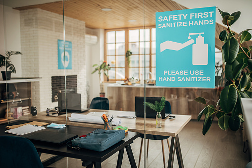 Safety「Safety first, sanitize hands sign on glass in in empty modern office」:スマホ壁紙(14)