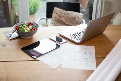 Working「Desk with laptop and cell phone next to construction plan and salad」:スマホ壁紙(8)