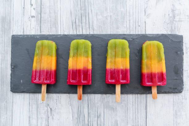 Row of four homemade fruit smoothie ice lollies on slate:スマホ壁紙(壁紙.com)