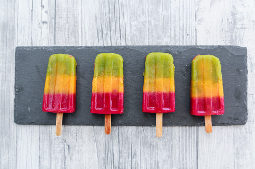 Equality「Row of four homemade fruit smoothie ice lollies on slate」:スマホ壁紙(2)