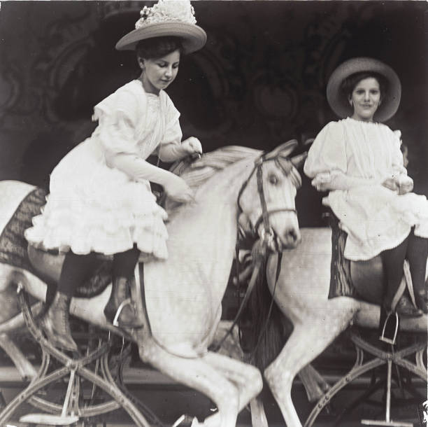 Two girls riding on merry-go-round-horses at the Viennese Wurstelprater. Vienna. Photograph by Emil Mayer. Hand-colored lantern slide. Around 1905-1910.:ニュース(壁紙.com)