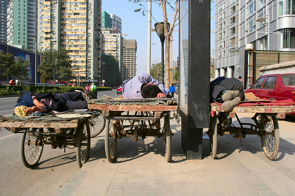 Coffee Break「Migrant labourers sleep on tricycle pallets during a lunch break in the central CBD area of Beijing.」:写真・画像(2)[壁紙.com]