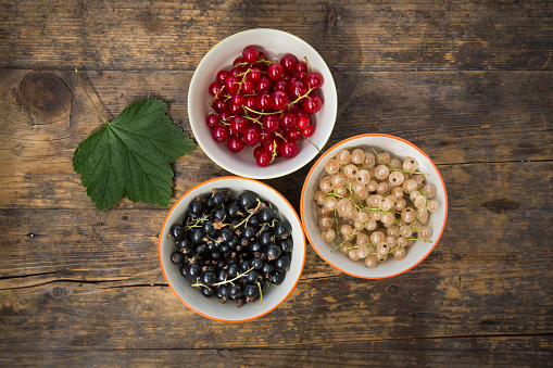 Black currant「Three bowls of red, white and black currants and a leaf on dark wood」:スマホ壁紙(3)