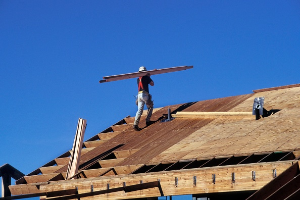 Carpentry「Carpenter carrying lumber on roof of large wood frame structure for community college」:写真・画像(5)[壁紙.com]
