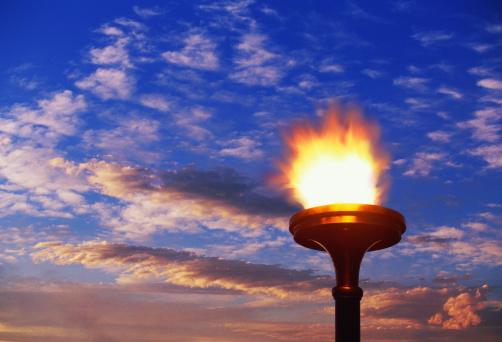 聖火「Flaming torch against cloudy sky, sunset (Digital Composite)」:スマホ壁紙(0)