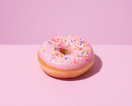 Indulgence「Pink doughnut with sprinkles on a pink background.」:スマホ壁紙(9)