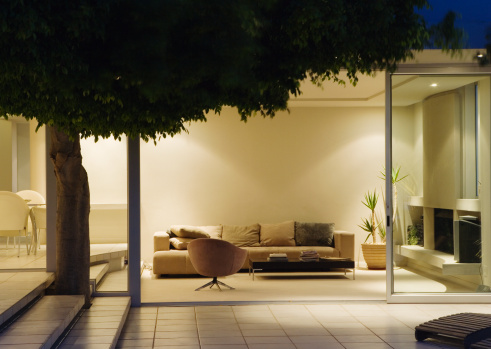 Night「Modern living room and patio with sliding glass walls」:スマホ壁紙(4)