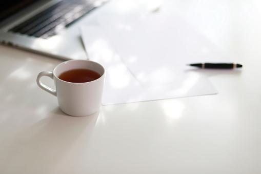 温かいお茶「Cup of coffee and laptop with papers on table」:スマホ壁紙(6)