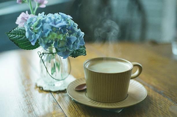 A cup of coffee next to a vase of hydrangeas:スマホ壁紙(壁紙.com)