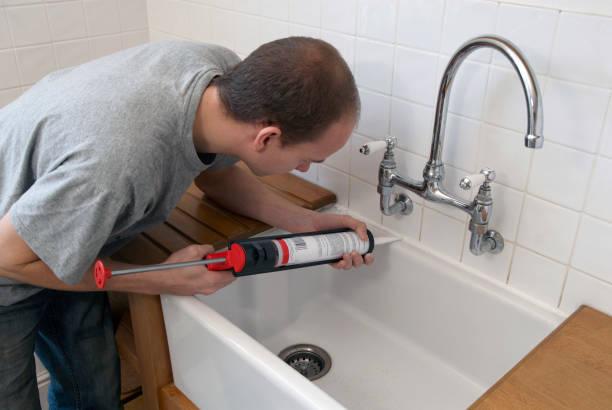 Man using sealant gun in a kitchen:ニュース(壁紙.com)