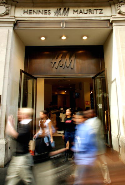 Defocused「Pedestrians Walk In Front Of The Swedish Fashion Store Hennes & Mauritz (H&M)」:写真・画像(1)[壁紙.com]
