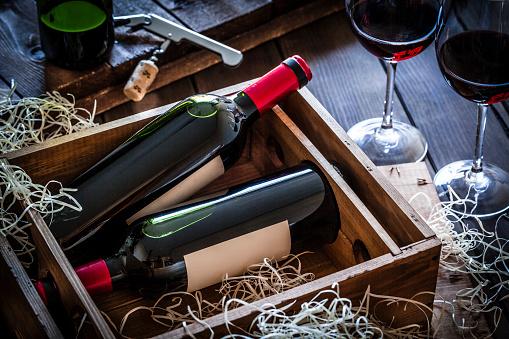 Bottle「Wine bottles packed in a wooden box shot rustic wooden table」:スマホ壁紙(11)