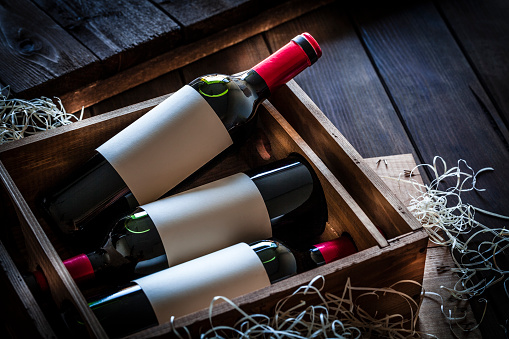 Wine Bottle「Wine bottles packed in a wooden box shot rustic wooden table」:スマホ壁紙(9)