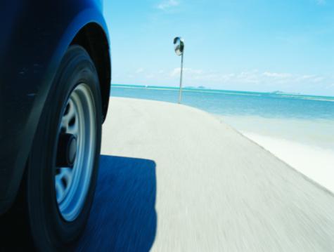 Motor Vehicle「Car driving on road along ocean (focus on wheel)」:スマホ壁紙(12)