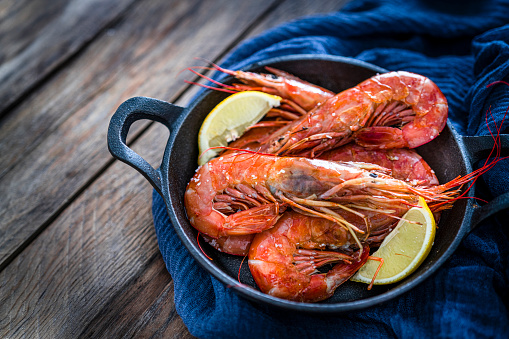 Cast Iron「Cooked shrimp in a cast iron cooking pan shot on wooden table. Copy space」:スマホ壁紙(16)
