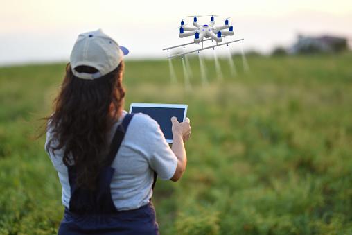 農業「ドローンを使用して彼女の作物を散布農家の若い女性」:スマホ壁紙(19)