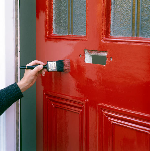 Painting a front door with bright red paint:ニュース(壁紙.com)