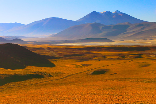 Antofagasta Region「Country dirt road crossing Chilean Andes altiplano at sunrise and volcano, Idyllic Atacama Desert, snowcapped Volcanic steppe puna landscape panorama – Antofagasta region, Chilean Andes, Chile, Bolívia and Argentina border」:スマホ壁紙(9)