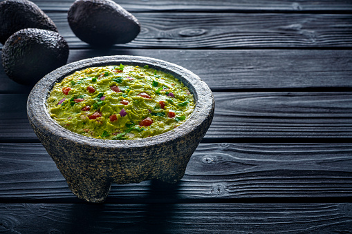 Recipe「Guacamole avocado Mexican recipe in stone molcajete on black wood background」:スマホ壁紙(19)