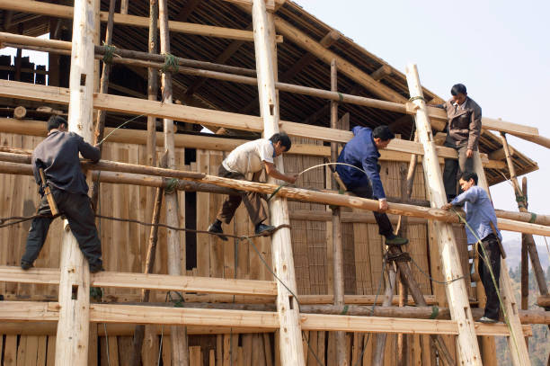Workers erecting a traditional timber house in traditional design of Dong ethnic minority people in Guangxi Province in China:ニュース(壁紙.com)
