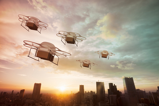 Autonomous Technology「Five delivery drones flying above the city at sunset」:スマホ壁紙(17)