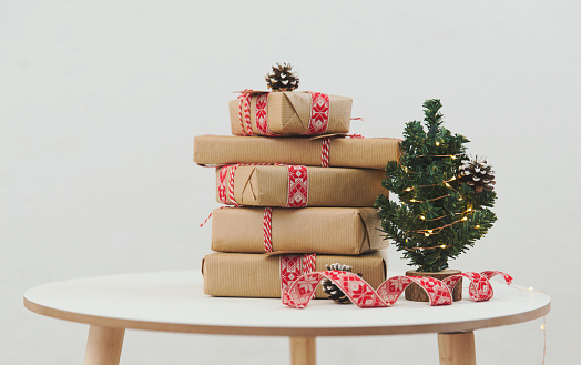 Gift「Stack of wrapped Christmas gifts next to a miniature Christmas tree」:スマホ壁紙(19)