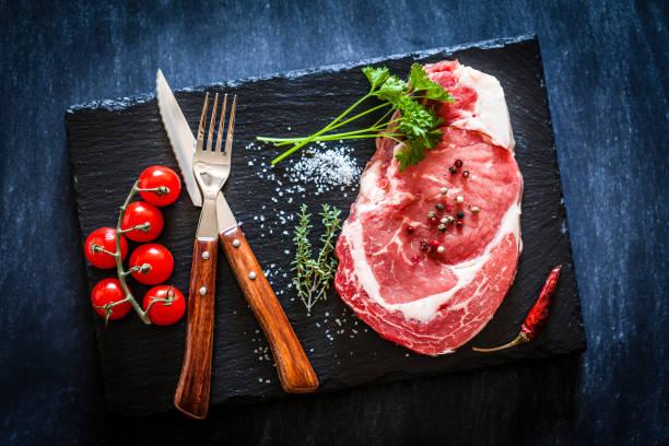 暗いスレート背景に新鮮な生の牛肉ステーキ:スマホ壁紙(壁紙.com)