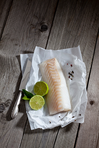 Raw Food「Filet of codfisch, lime and knife, and peppercorns on greaseproof paper on wood」:スマホ壁紙(0)