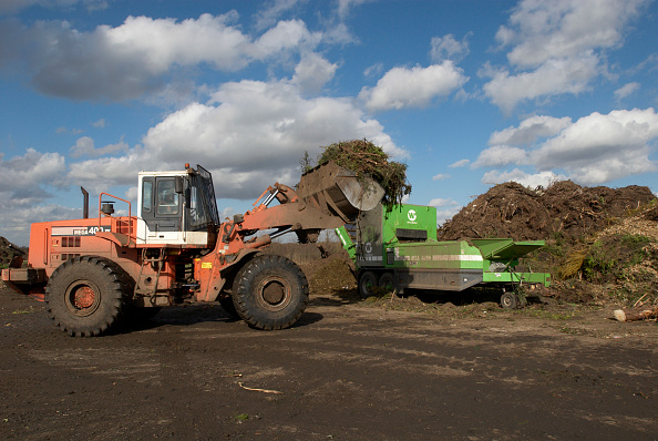 Pouring「Front loader emptying garden waste into composting plant at site for recycling food and garden waste, Suffolk, UK」:写真・画像(2)[壁紙.com]