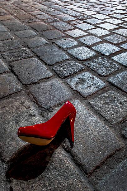 Red high heel lying on cobblestone pavement at night:スマホ壁紙(壁紙.com)