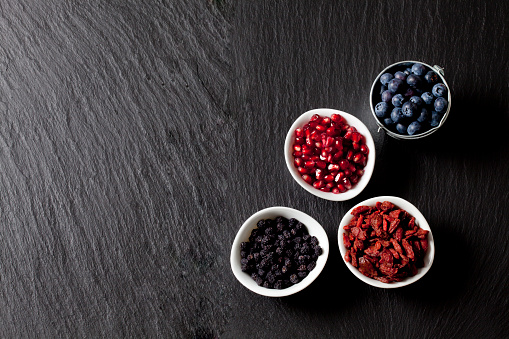 Pomegranate「Bowls of blueberries, pomegranate seed, goji berries and chokeberries on slate」:スマホ壁紙(5)