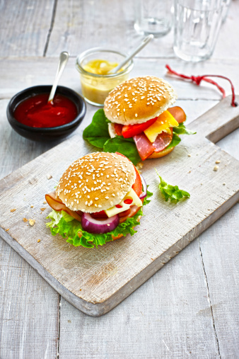 Hamburger「Two prepared burgers, mustard and ketchup on wooden ground」:スマホ壁紙(3)