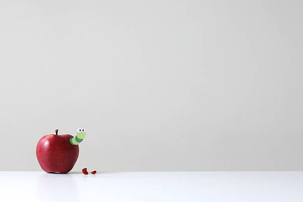 A red apple with a green paper worm poking out:スマホ壁紙(壁紙.com)