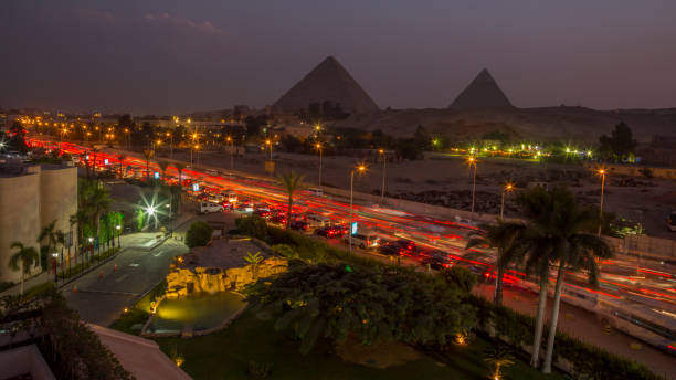 the traffic of the Cairo and view on the pyramids at night:スマホ壁紙(壁紙.com)