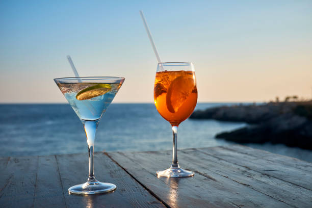 Glass of ice-cooled Spritz with orange slice and glass of Martini with lime slice in front of the sea:スマホ壁紙(壁紙.com)