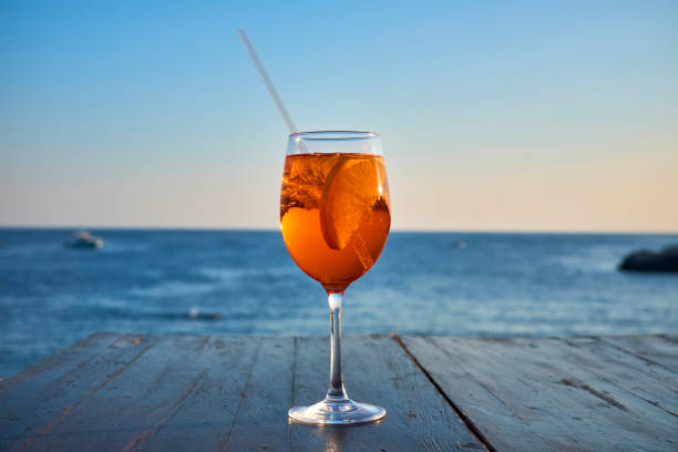 Glass of ice-cooled Spritz with orange slice in front of the sea:スマホ壁紙(壁紙.com)
