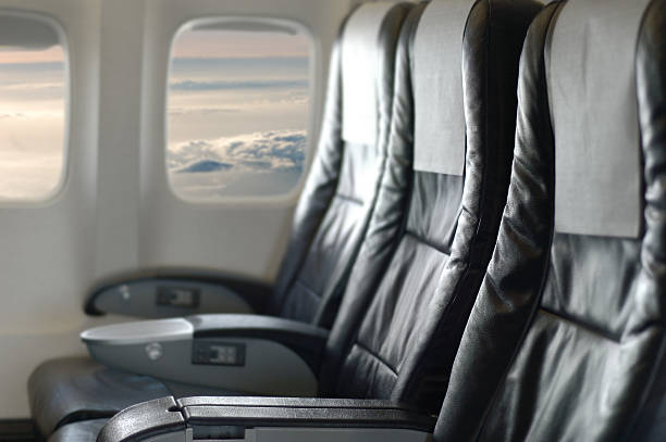Three black aircraft seats looking out of the window:スマホ壁紙(壁紙.com)