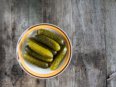 Pickle「Pickled green gherkins in a bowl on a wooden table」:スマホ壁紙(6)