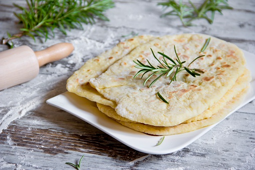 Naan Bread「Stack of naan breads with rosemary twig on plate」:スマホ壁紙(14)